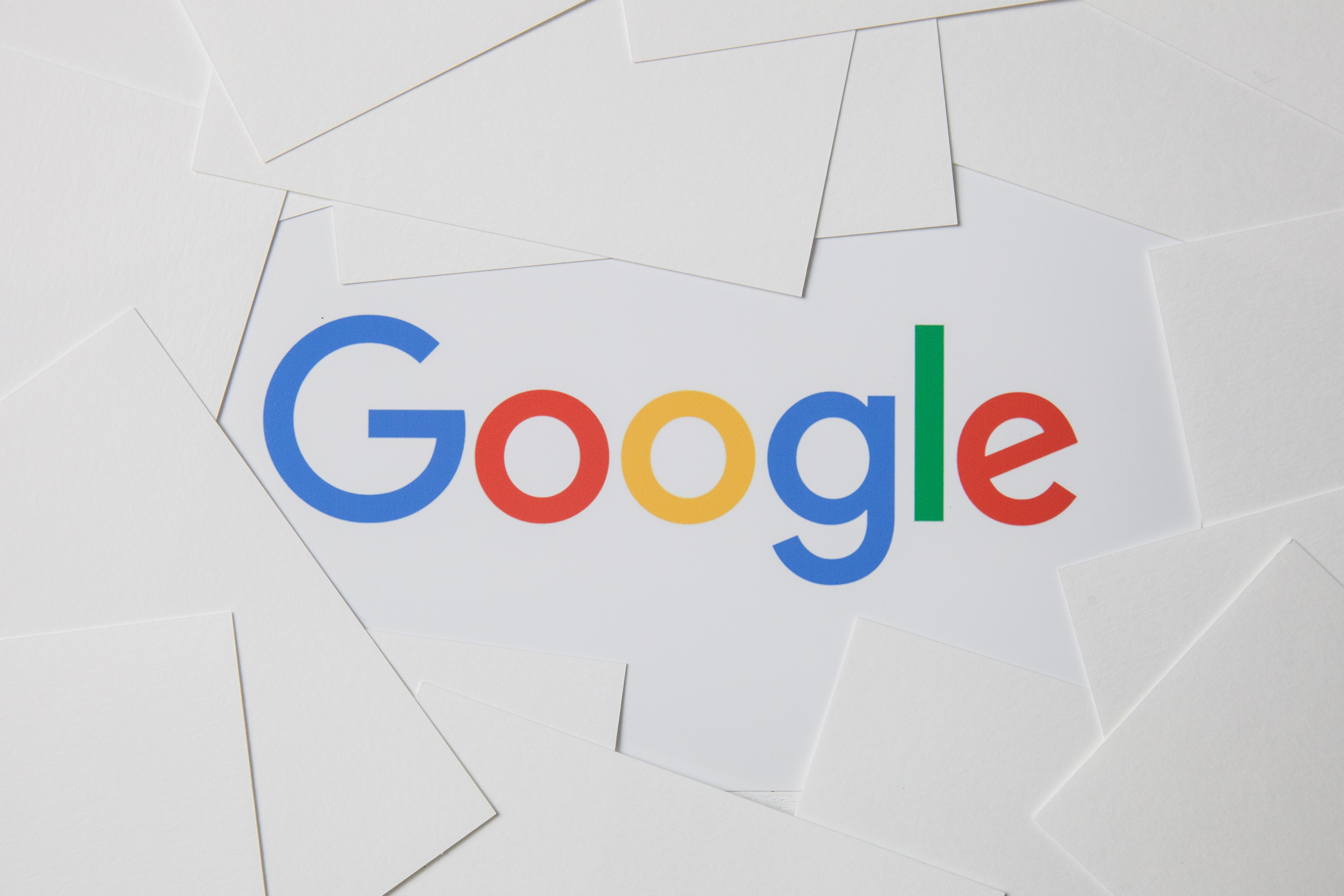 Photo of logo of Google on printing paper on the working table.